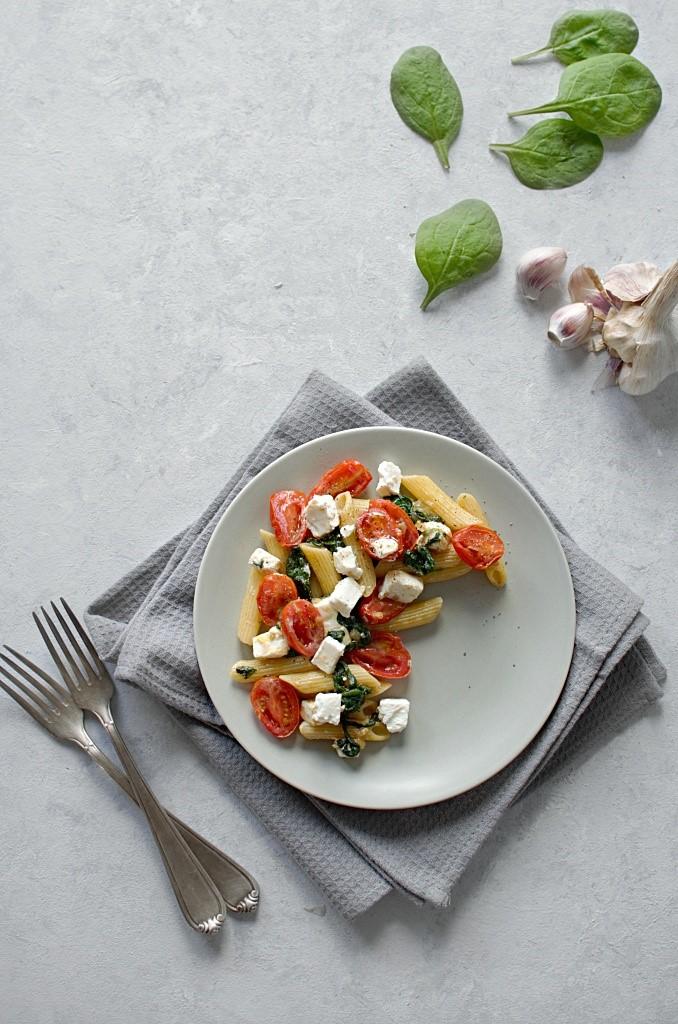 Makaron ze szpinakiem i serem feta i pomidorkami.